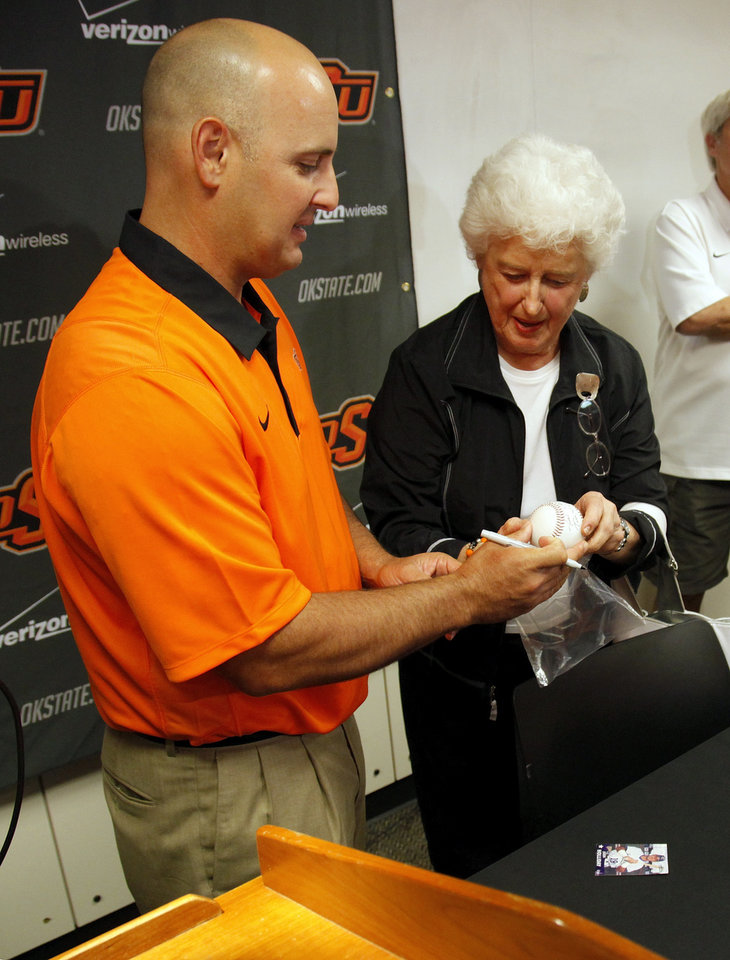 Photo - Josh Holliday signs a baseball for Jo Martindale after a press conference at Oklahoma State University to introduce Josh Holliday as OSU's new head baseball coach, in Stillwater, Okla., Friday, June 8, 2012. Martindale was a neighbor of the Holliday family when they previously lived in Stillwater. Photo by Nate Billings, The Oklahoman