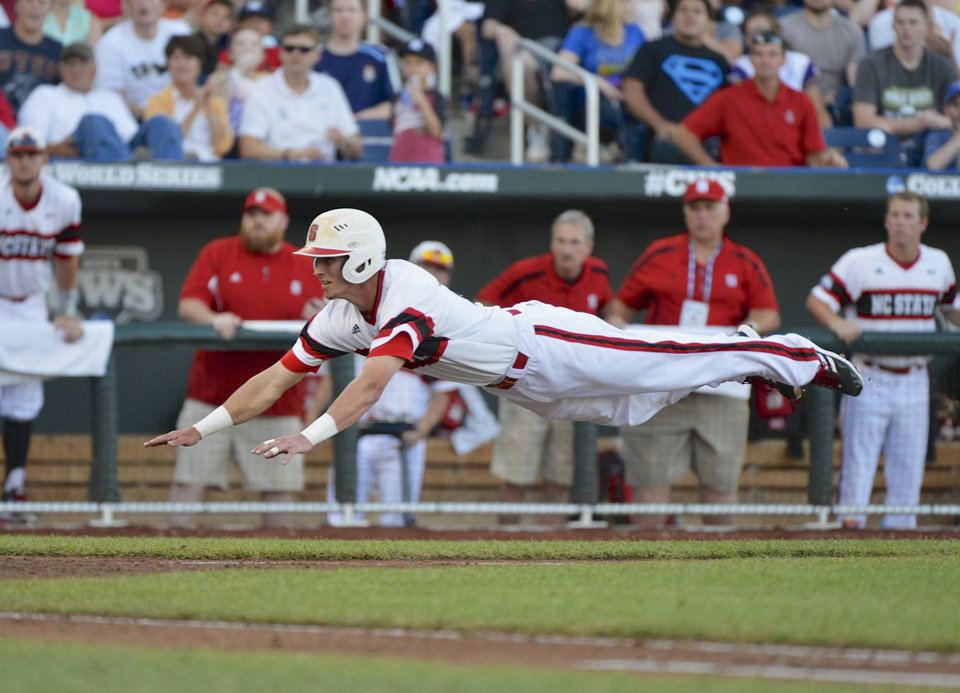 Photo - North Carolina State's Jake Armstrong leaps towards home plate before being tagged out by UCLA pitcher Nick Vander Tuig, following a single by Trea Turner in the third inning of an NCAA College World Series game in Omaha, Neb., Tuesday, June 18, 2013. (AP Photo/Ted Kirk)