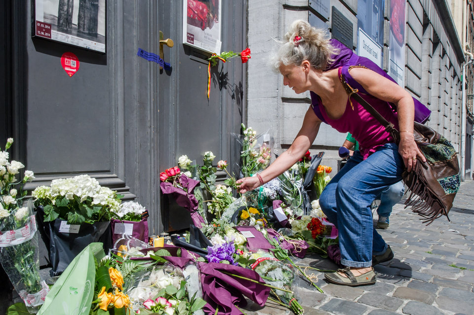 Photo - A woman lays flowers at the Jewish Museum in Brussels, Sunday May 25, 2014.  Police stepped up security at Jewish institutions, schools and synagogues after three people were killed and one seriously injured in a spree of gunfire at the Jewish Museum in Brussels on Saturday. (AP Photo/Geert Vanden Wijngaert)