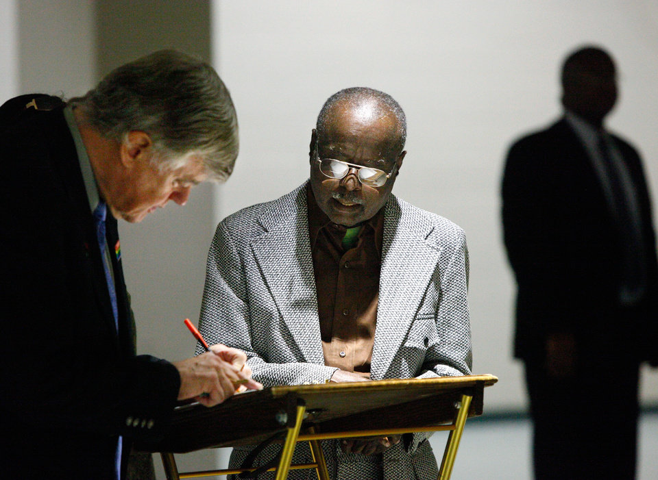 Photo - CLARA LUPER / MEMORIAL SERVICE / DEATH:  Nathaniel Batchelder sign the guest book as Richard Cotton, 72 of Oklahoma City, waits to sign his name. Cottom said he was a friend of Luper and marched with her during the civil rights movement. He also participated in downtown sit-ins. About 2,500 people celebrated the life and legacy of Oklahoma City civil rights pioneer Clara Mae Shepard Luper  during a lively service in the Cox Convention Center that lasted more than three hours, Friday,  June 17, 2011.  Luper died  last week at the age of 88. Photo by Jim Beckel, The Oklahoman ORG XMIT: KOD