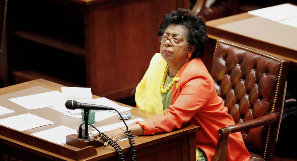 Photo - State Sen. Judy Eason McIntyre, D-Tulsa, reaches across her desk to vote after debate on an override of an abortion bill on the Senate floor in Oklahoma City Tuesday, April 27, 2010. The Oklahoma Senate voted 36-12 to override Gov. Brad Henry's veto of two abortion bills. Photo by Paul B. Southerland, The Oklahoman ORG XMIT: KOD
