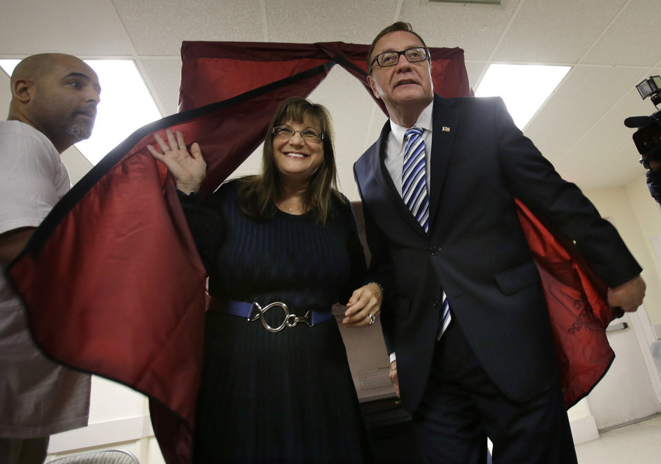 Photo - Lorraine Rossi Lonegan exits a voting booth with her husband Republican senate candidate Steve Lonegan, in Bogota, N.J., Wednesday, Oct. 16, 2013.  Lonegan and Democrat Cory Booker are vying to fill the Senate seat left vacant by the death of Frank Lautenberg. (AP Photo/Mel Evans)