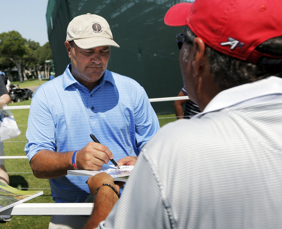 Photo - Rocky Walcher signs an autograph during practice rounds for the U.S. Senior Open golf tournament at Oak Tree National in Edmond, Okla., Monday, July 7, 2014. Photo by Nate Billings, The Oklahoman