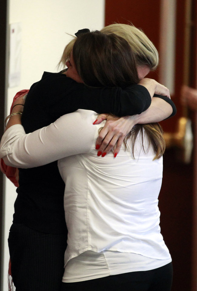 Unidentified women embrace outside of the courtroom in the case of Aurora theater shooting suspect James Holmes in Centennial, Colo., on Monday, April 1, 2013, after hearing that the prosecution will seek the death penalty in the case against Holmes. (AP Photo/Brennan Linsley)