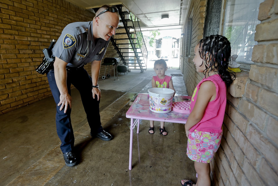 Photo -  Mark Garrett, with Oklahoma City police's Hefner Patrol Division, talks to children that live at Windsor Village Apartments as he patrols the area Tuesday. Photos by Chris Landsberger, The Oklahoman      -