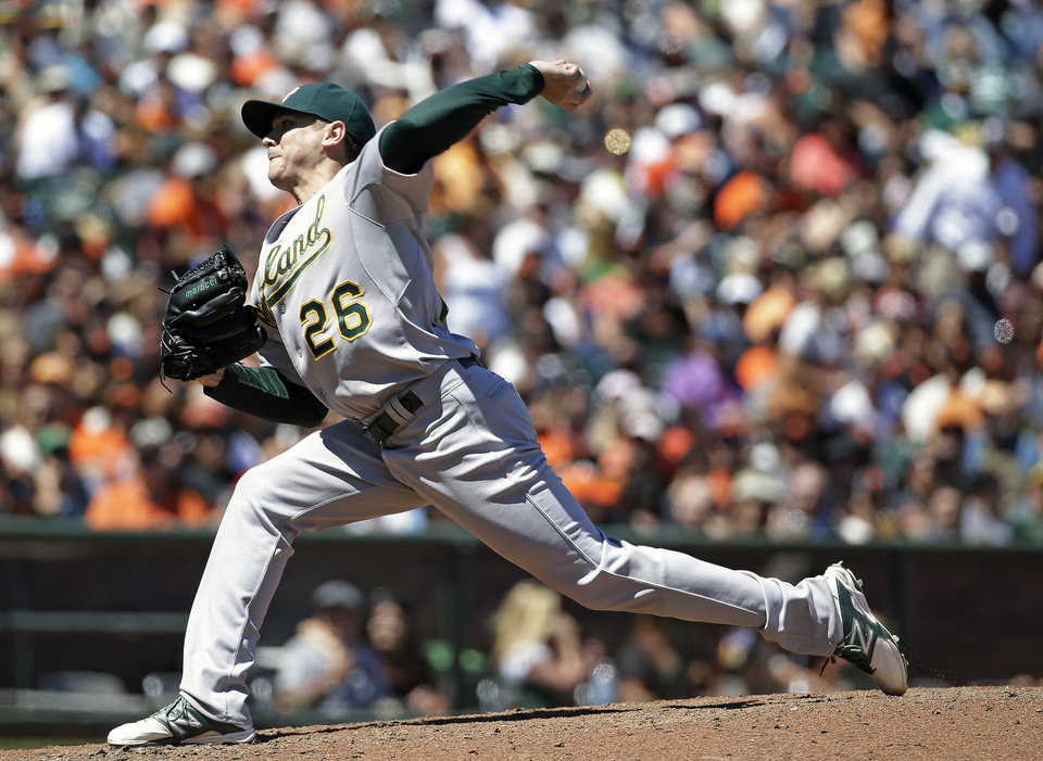 Photo - Oakland Athletics starting pitcher Scott Kazmir throws against the San Francisco Giants in the sixth inning of their interleague baseball game Thursday, July 10, 2014, in San Francisco. Oakland won the game 6-1 and Kazmir struck out nine in seven scoreless innings. (AP Photo/Eric Risberg)