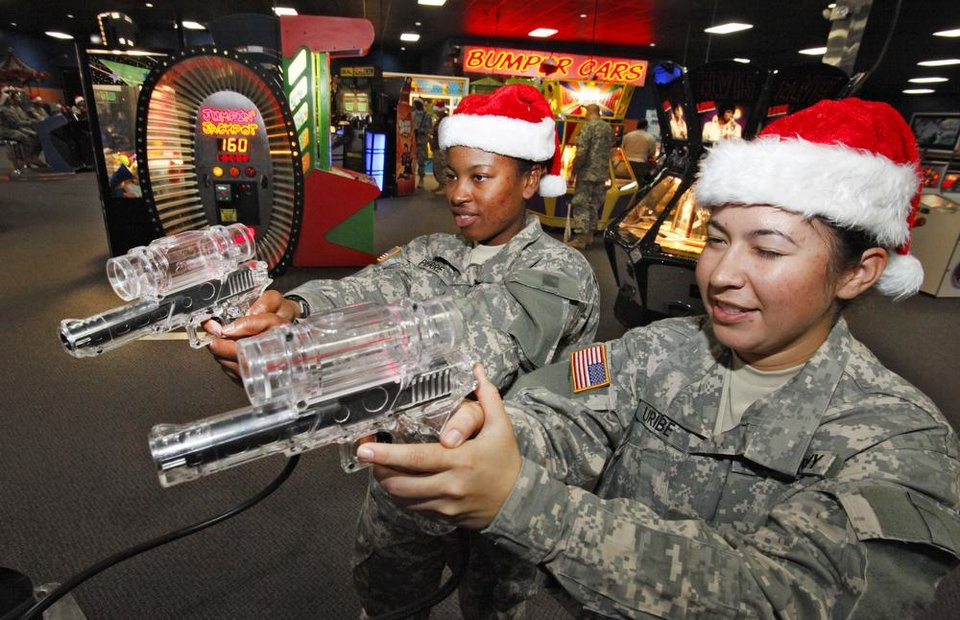 New recruits Pfc Ashly Pierre and Isabella Uribe play a shooting game during a lunch stop at Gatti Town during Soldiers Day Out, Friday, December 21, 2012. Edmond/North OKC Blue Star Mothers will be taking the soldiers who can't go home for Christmas around the metro for a day of fun. Photo By David McDaniel/The Oklahoman
