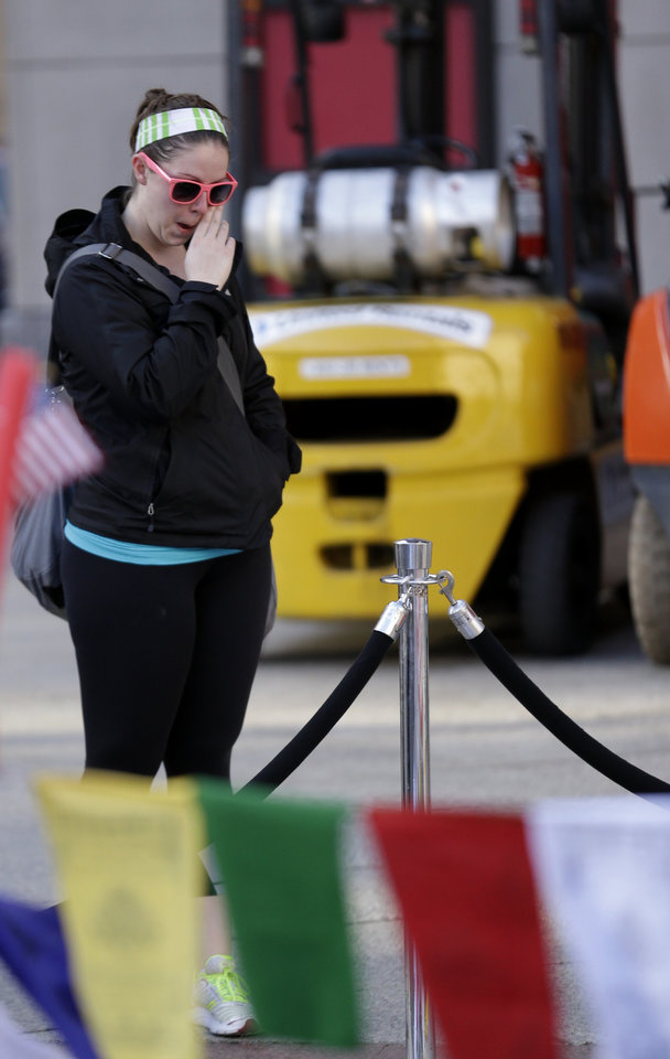 A woman cries at a makeshift memorial on Boylston Street in Boston, near the blast site of the Boston Marathon explosions, Thursday, April 18, 2013. The city continues to cope following Monday's explosions near the finish line of the marathon. (AP Photo/Julio Cortez)