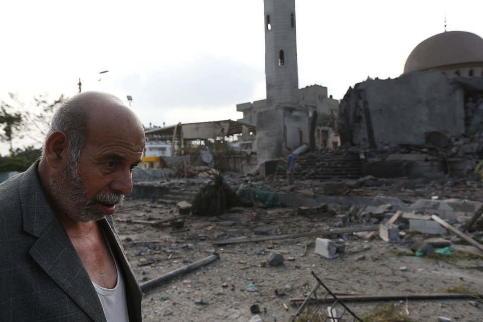 Photo - Palestinian Khaled Sharmi, 67, walks past the Al Aqsa Martyrs mosque, destroyed by an overnight Israeli strike, in Gaza City Tuesday, July 22, 2014. Israel bombed five mosques, a sports stadium and the home of the late Hamas military chief across the Gaza Strip early on Tuesday, a Gaza police official said, as the U.N. chief Ban Ki-moon and the U.S. Secretary of State John Kerry launched a high-level effort to end two weeks of deadly fighting. (AP Photo/Lefteris Pitarakis)