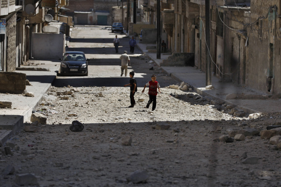 Photo -   Two Syrian boys play on a street next to a building hit by a Syrian government airstrike in Aleppo, Syria, Sunday, Aug. 19, 2012 (AP Photo/ Khalil Hamra)