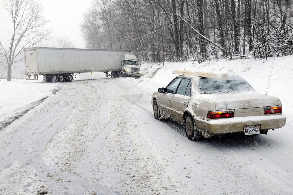 Photo - A jackknifed tractor-trailer blocks the eastbound lanes of Route 7 near the Clarke-Frederick County, Va. State line during a snow storm Tuesday, Jan. 21, 2014. (AP Photo/The Winchester Star, Scott Mason)