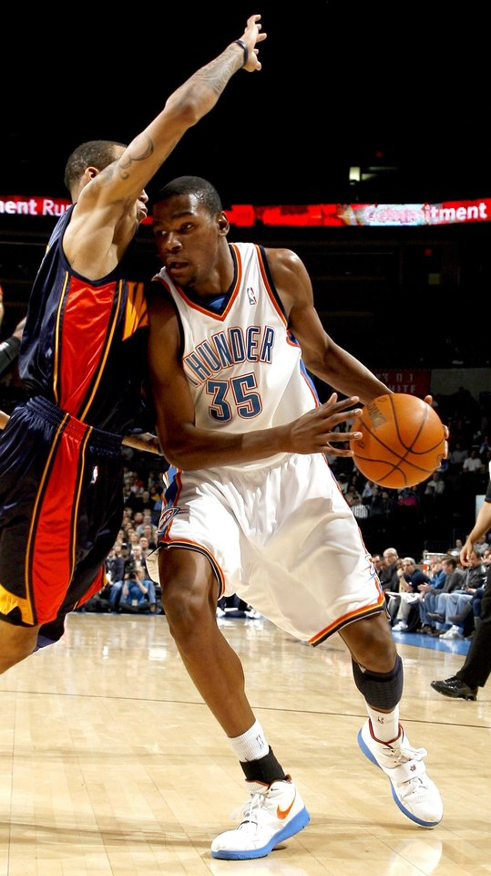 Photo - Oklahoma City's Kevin Durant (35) looks to get around Monta Ellis (8) during the NBA game between the Oklahoma City Thunder and Golden State Warriors, Sunday, Jan. 31, 2010, at the Ford Center in Oklahoma City. Photo by Sarah Phipps, The Oklahoman
