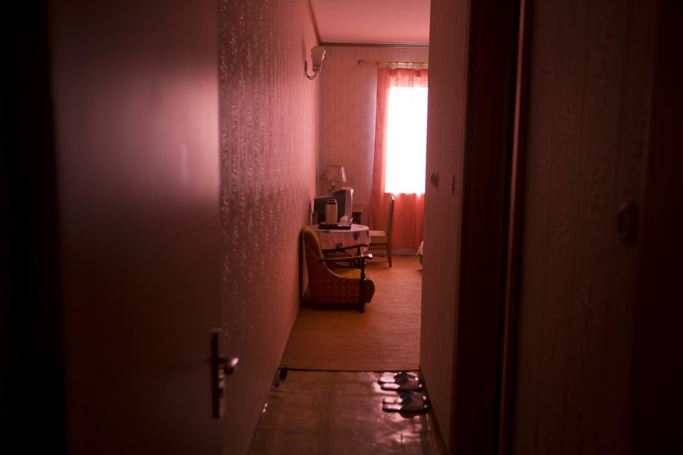 In this Sept. 11, 2012 photo, a guest room is bathed in red light shining through a curtain at a hotel for foreign tourists in Kaesong, North Korea. (AP Photo/David Guttenfelder)