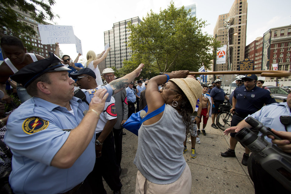 Photo - Police try to stop a woman wielding a cane from hitting another woman, not pictured, who was supporting Israel in its war with Hamas members in the Gaza Strip, during a rally at John F. Kennedy Plaza, also known as Love Park, in Philadelphia on Wednesday, July 23, 2014. (AP Photo)