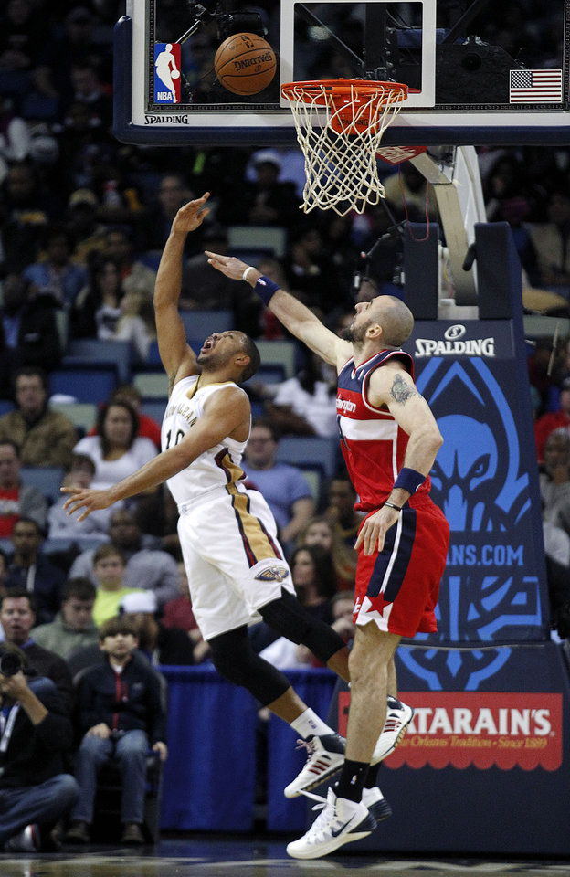 Photo - New Orleans Pelicans shooting guard Eric Gordon (10) is fouled by Washington Wizards center Marcin Gortat as he goes to the basket in the first half of an NBA basketball game in New Orleans, Wednesday, Jan. 8, 2014. (AP Photo/Gerald Herbert)