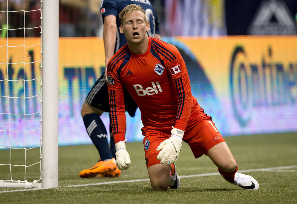 Photo - Vancouver Whitecaps goalkeeper David Ousted, of Denmark, reacts after allowing a goal to Portland Timbers' Alvas Powell, of Jamaica, during the second half of an MLS soccer game in Vancouver, British Columbia, on Saturday, Aug. 30, 2014. (AP Photo/The Canadian Press, Darryl Dyck)
