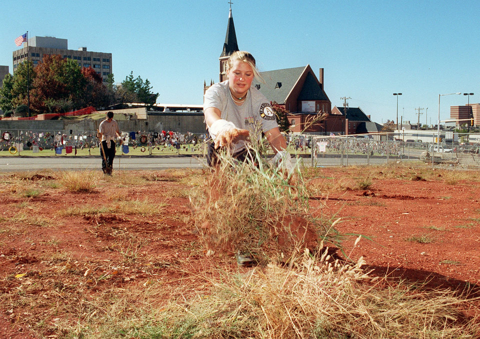 Photo - Oct. 29, 1996: Lisa Perkins of Concord, Ohio, clears weeds from the empty lot just north of the Alfred P. Murrah Federal Building explosion site in downtown Oklahoma City. Perkins was part of the National Civilian Community Corps Sun Team No. 1, a group that is part of the NCCC out of Denver, Colo., provided through the AmeriCorps program. [Photo by Roger Klock, The Oklahoman]