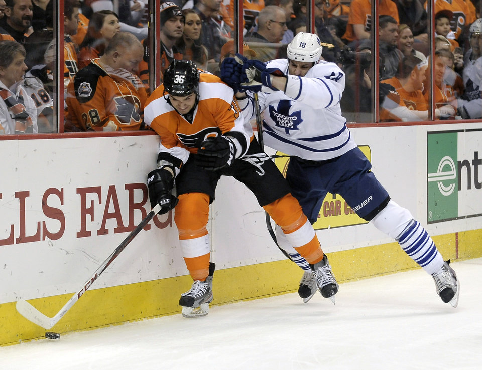 Toronto Maple Leafs' Mike Brown, right, checks Philadelphia Flyers' Ruslan Fedotenko, of Ukraine, in the first period of an NHL hockey game, Monday, Feb 25, 2013, in Philadelphia. (AP Photo/Michael Perez)