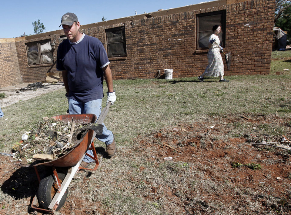 Photo - Matt Boehs, left, and Jerilyn Boehs, volunteers with Christian Disaster Relief through the Church of God in Christ Menonnite, help to clean up debris in Woodward, Okla., Monday, April 16, 2012.  A tornado struck the town early Sunday morning. Photo by Nate Billings, The Oklahoman
