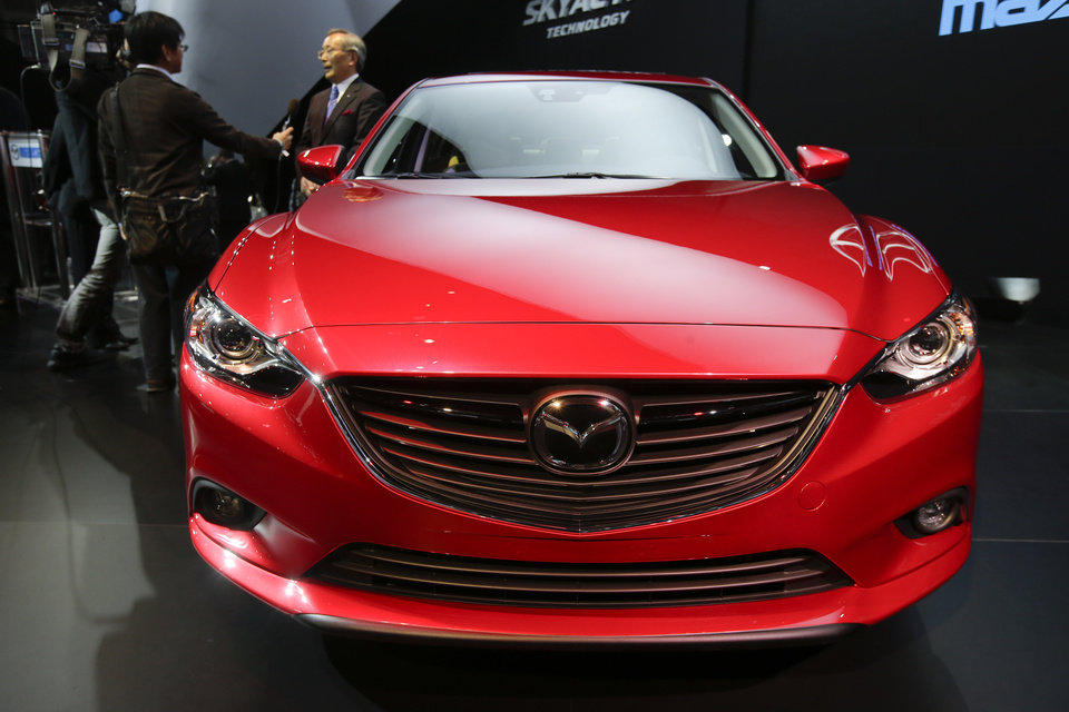 Mazda CEO Takashi Yamanouchi is interviewed while the Mazda6 is shown during it's North American debut at the LA Auto Show in Los Angeles, Thursday, Nov. 29, 2012. (AP Photo/Chris Carlson)