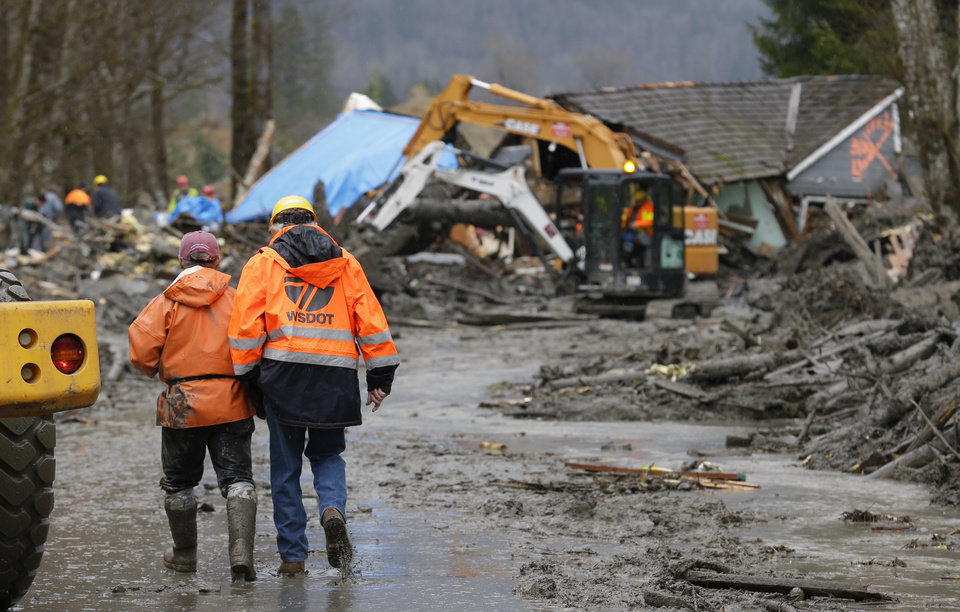 Photo - Workers walk through mud as heavy equipment operators work to clear debris Tuesday, March 25, 2014, from Washington Highway 530 on the western edge of the massive mudslide that struck the area Saturday, killing at least 14 people and leaving dozens missing. (AP Photo/Ted S. Warren, Pool)