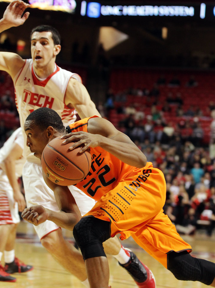 Photo - Oklahoma State's Markel Brown 922) drives against Texas Tech's Dejan Kravic during their NCAA college basketball game, Wednesday, Feb. 13, 2013, in Lubbock, Texas. (AP Photo/The Avalanche-Journal, Zach Long) ALL LOCAL TV OUT