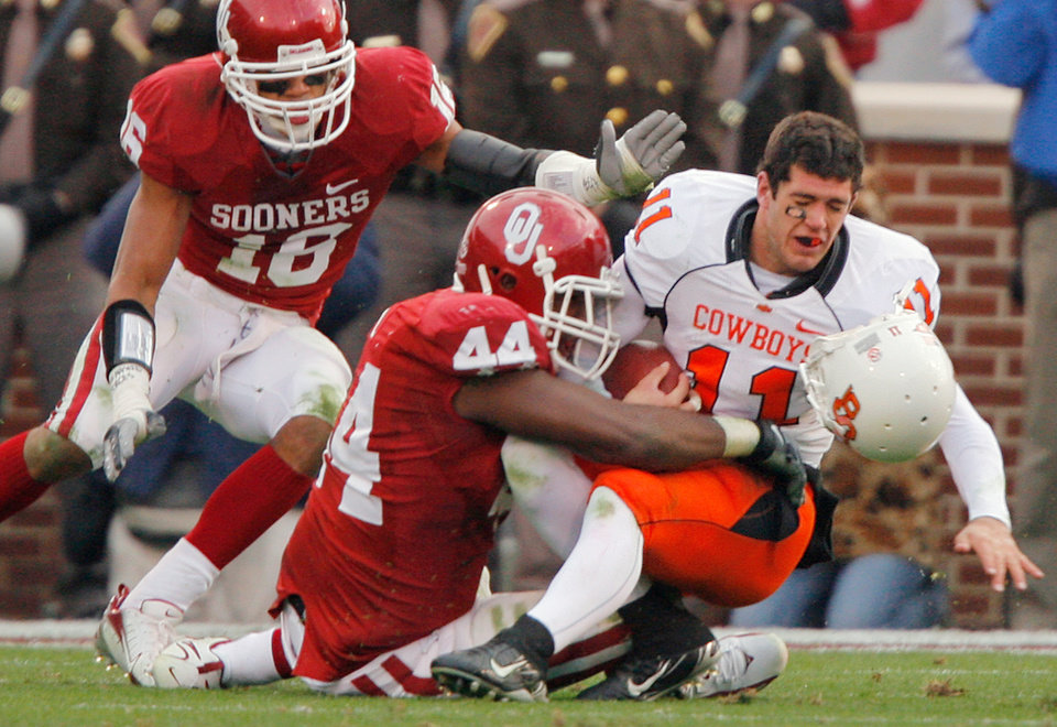 Photo - Oklahoma State quarterback Zac Robinson (11) has his helmet knocked off by Oklahoma's Jeremey Beal (44) during the first half of the college football game between the University of Oklahoma Sooners (OU) and the Oklahoma State University Cowboys (OSU) at the Gaylord Family-Memorial Stadium on Saturday, Nov. 24, 2007, in Norman, Okla. 