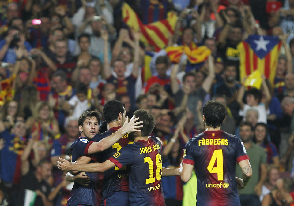 FC Barcelona's Lionel Messi from Argentina, left, celebrates his goal with team mates during a Spanish La Liga soccer match against Real Madrid at the Camp Nou stadium in Barcelona, Spain, Sunday, Oct. 7, 2012. (AP Photo/Andres Kudacki)