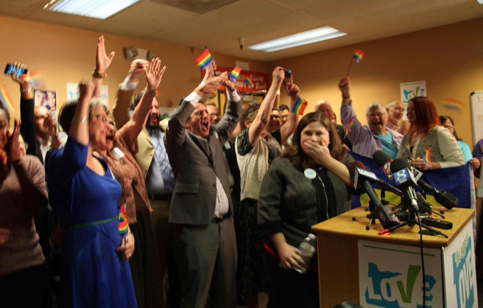 Photo - Gay and lesbian couples and their supporters react to the news of a federal judge striking down Oregon's ban on same-sex marriage at the headquarters of Oregon United for Marriage Monday, May 19, 2014, in Portland, Ore. Jubilant couples are rushing to the altar after a federal judge struck down Oregon's ban on same-sex marriage. The ruling from Judge Michael McShane came shortly after noon. Couples across the state quickly started getting marriage licenses and, in some cases, going through with the ceremony.(AP Photo/Gosia Wozniacka)