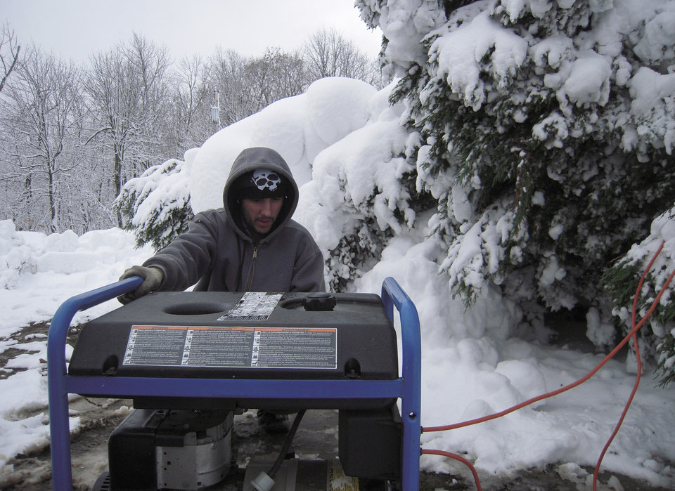 Photo -   Garrett Colmer works on a generator outside his stepfatherís home in unincorporated Finzel, near Frostburg, Md., on Wednesday, Oct. 31, 2012. The vast majority of homes in mountainous, western Maryland Garrett county lost power after superstorm Sandy dumped more than 2 feet of snow in the area. (AP Photo/David Dishneau)