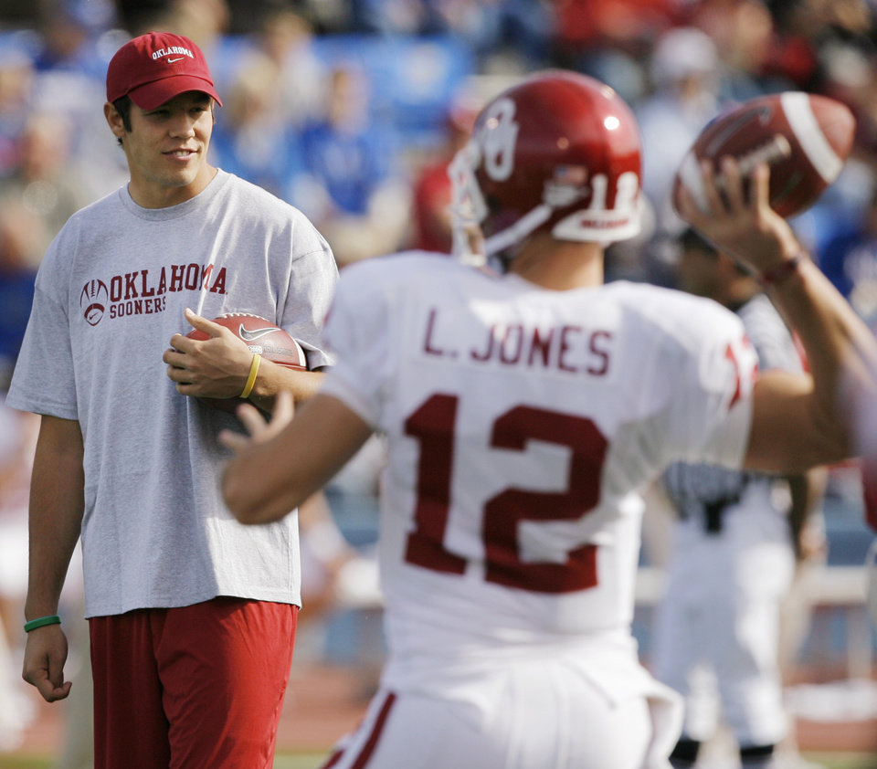 Photo - OU's Landry Jones (12) warms up in front of Sam Bradford before the college football game between the University of Oklahoma Sooners (OU) and the University of Kansas Jayhawks (KU) on Saturday, Oct. 24, 2009, in Lawrence, Kan. OU won, 35-13. Photo by Nate Billings, The Oklahoman