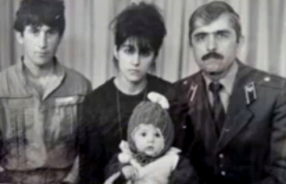 Photo - In this image taken from a video, an undated family photo provided by Patimat Suleimanova, the aunt of USA Boston bomb suspects, shows Anzor Tsarnaev left, Zubeidat Tsarnaev holding Tamerlan Tsarnaev and Anzor's brother Mukhammad Tsarnaev. Now known as the angry and grieving mother of the Boston Marathon bombing suspects, Zubeidat Tsarnaev is drawing increased attention after federal officials say Russian authorities intercepted her phone calls, including one in which she vaguely discussed jihad with her elder son. In another, she was recorded talking to someone in southern Russia who is under FBI investigation in an unrelated case, U.S. officials said. (AP Photo/Patimat Suleimanova)