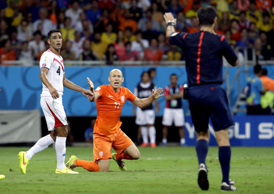 Photo - Netherlands' Arjen Robben, center, reacts during the World Cup quarterfinal soccer match between the Netherlands and Costa Rica at the Arena Fonte Nova in Salvador, Brazil, Saturday, July 5, 2014. At left Costa Rica's Michael Umana.(AP Photo/Hassan Ammar)