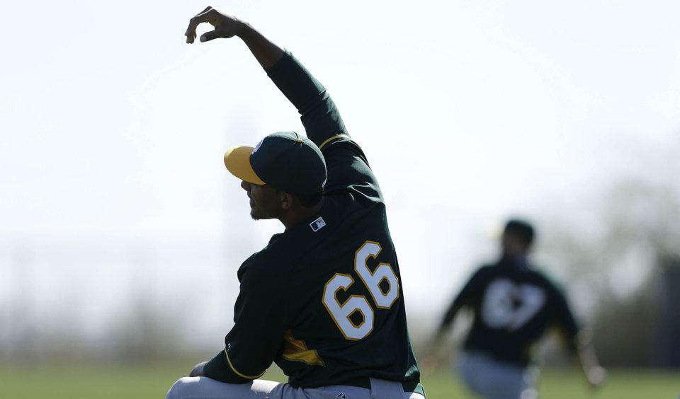 Photo - Oakland Athletics Michael Ynoa stretches during spring training baseball practice Saturday, Feb. 15, 2014, in Scottsdale, Ariz.  (AP Photo/Gregory Bull)