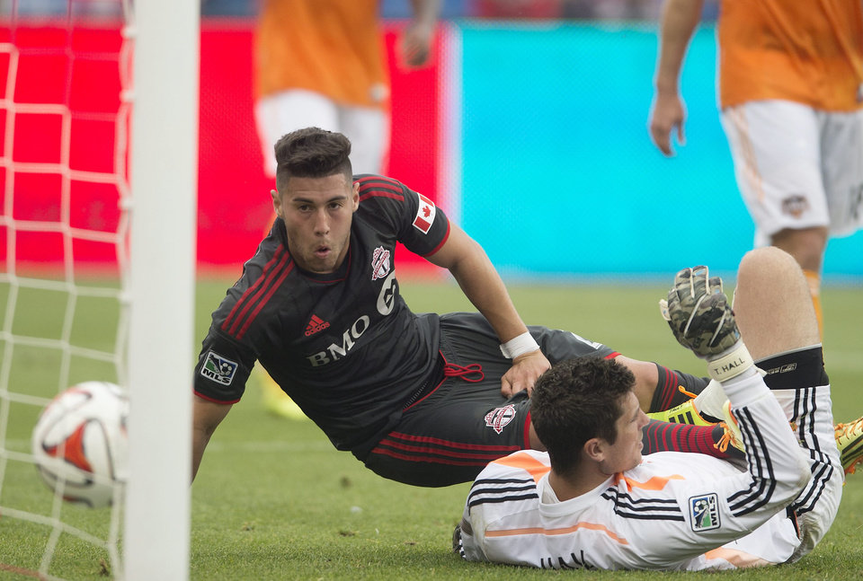 Photo - Toronto FC's Jonathan Osorio, left, watches the ball roll into the goal past Houston Dynamo goalkeeper Tally Hall during the first half of a soccer game, Saturday, July 12, 2014 in Toronto. (AP Photo/The Canadian Press, Darren Calabrese)