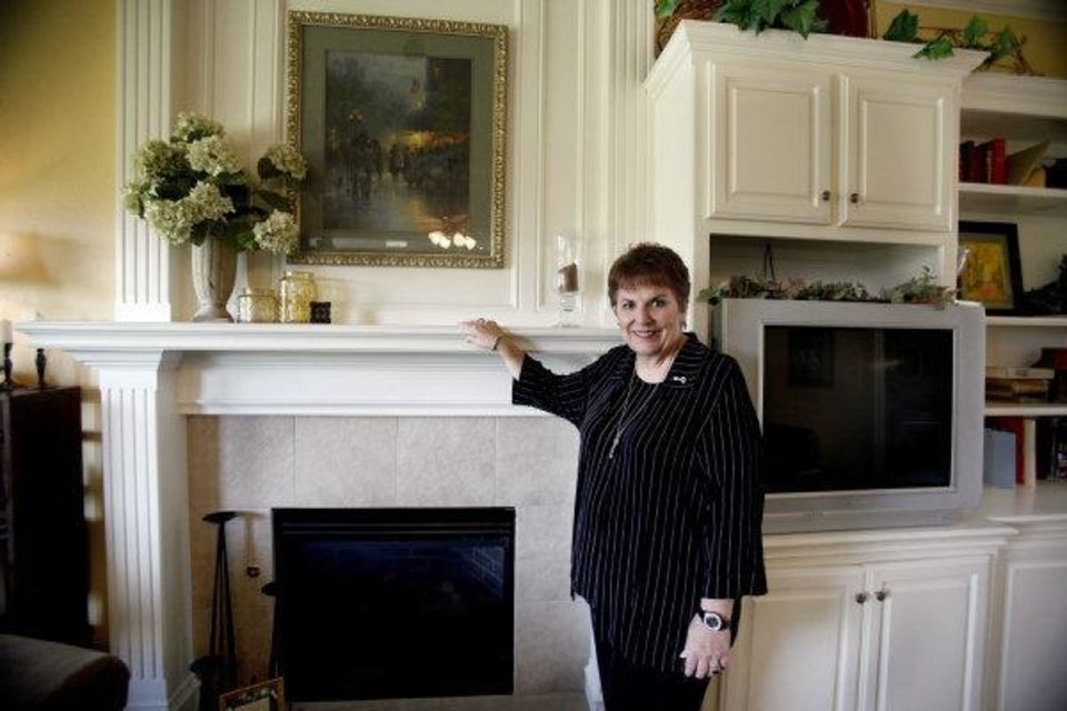 Photo - Linda Finch, a Realtor with Paradigm AdvantEdge Real Estate, shows the fireplace of a home she has listed for sale at 8501 NW 67.  SARAH PHIPPS - THE OKLAHOMAN