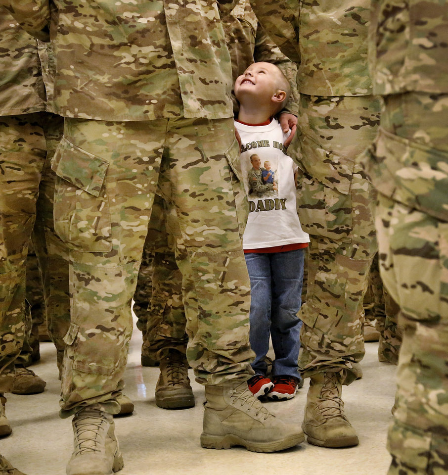 Photo - Although not even reaching his dad's waistline, Devon Hatfield stood tall and proud beside his dad, Sgt. Juston Hatfield, during the welcoming ceremony. Devon spotted his dad as the soldiers marched into the room and assembled in formation; he bolted toward his dad and remained with him during the entire ceremony. He smiled the entire time. Hatfield is from Tishomingo. At least 1,000 people, mostly spouses, children, relatives and friends, crowded into a large room in the Armed Forces Reserve Center in Norman on Saturday, Sep. 28, 2013, to give a boisterous, and at times, tearful welcome  to members of the Oklahoma National Guard who returned to Norman after 10 months in Afghanistan. After a brief ceremony, which included a personal thank-you to his troops from Maj. Gen. Myles Deering, the soldiers were dismissed to an emotional reunion with their love ones. Deering serves as adjutant general of Oklahoma.  Photo  by Jim Beckel, The Oklahoman.