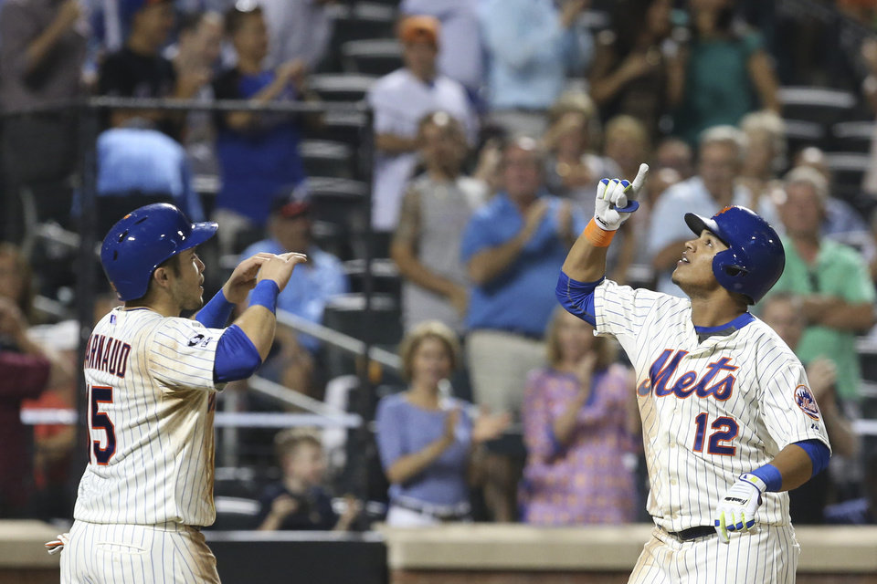 Photo - New York Mets' Juan Lagares (12) gestures alongside Travis d'Arnaud after hitting a two-run home run in the fourth inning of a baseball game against the Atlanta Braves on Tuesday, Aug. 26, 2014, in New York. (AP Photo/John Minchillo)
