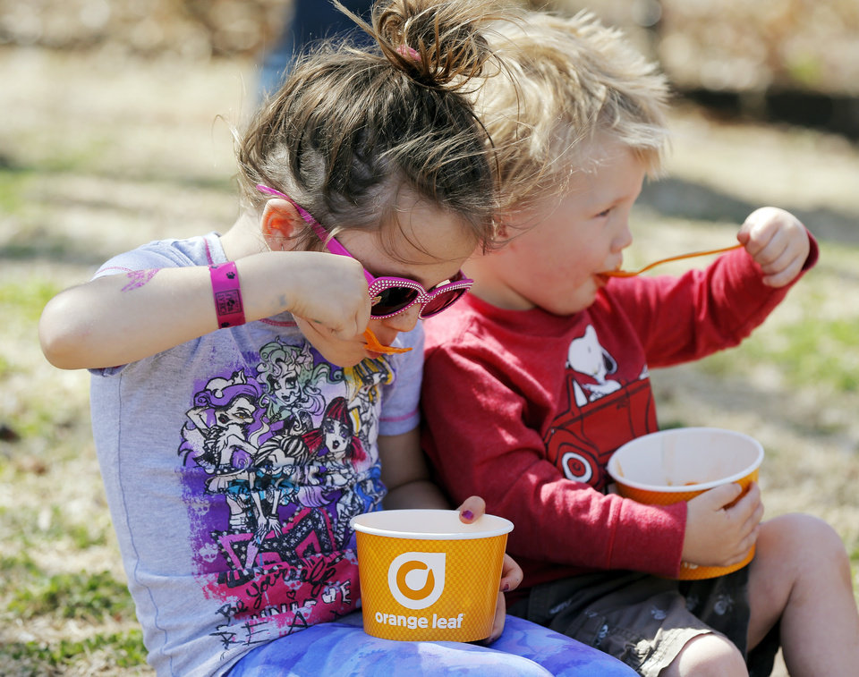 Photo - Aubrey Long, 6, left, and her brother, Charley Long, 2, eat frozen yogurt during the Open Streets OKC event along NW 23rd St. in Oklahoma City, Sunday, March 30, 2014. From noon until 4pm, NW 23rd St. between Robinson and Western was closed to cars for the event. Photo by Nate Billings, The Oklahoman