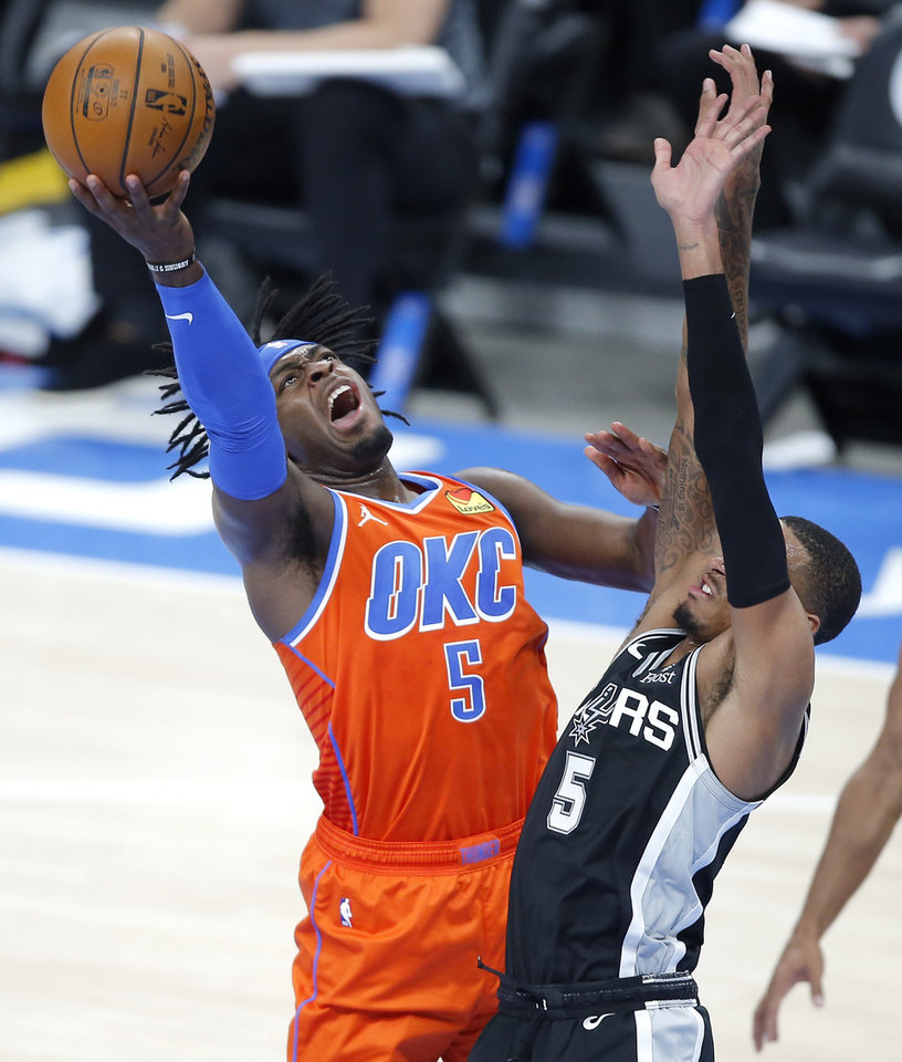 Photo - Oklahoma City's Luguentz Dort (5) goes to the basket as San Antonio's Dejounte Murray (5) defends during an NBA basketball game between the Oklahoma City Thunder and the San Antonio Spurs at Chesapeake Energy Arena in Oklahoma City, Tuesday, Jan. 12, 2021.  San Antonio won 112-102. [Bryan Terry/The Oklahoman]