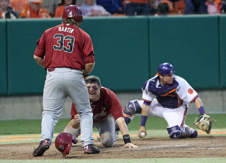 Photo - South Carolina's Grayson Greiner, center, celebrates with teammate Kyle Martin after diving around Clemson catcher Chris Okey, right, to score the tying run in an NCAA college baseball game on Sunday, March 2, 2014, in Clemson, S.C. (AP Photo/Anderson Independent-Mail, Mark Crammer) GREENVILLE NEWS OUT; SENECA NEWS OUT