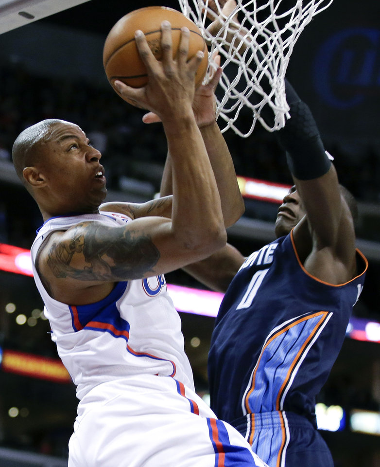 Photo - Los Angeles Clippers forward Caron Butler, left, shoots against Charlotte Bobcats forward Bismack Biyombo during the first half of an NBA basketball game in Los Angeles, Tuesday, Feb. 26, 2013. (AP Photo/Chris Carlson)