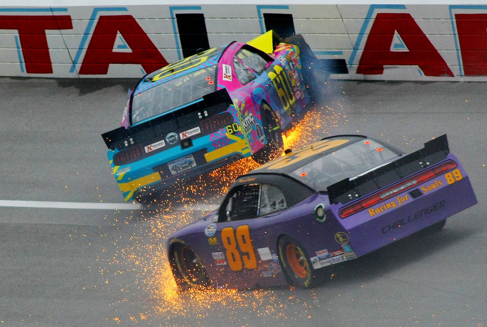 Photo - Travis Pastrana (60) crashes in Turn 3 along with Morgan Shepherd (89) during the NASCAR Nationwide Series auto race at the Talladega Superspeedway in Talladega, Ala., Saturday, May 4, 2013. (AP Photo/Greg McWilliams)
