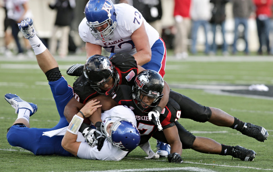 Photo -   CORRECTS SPELLING OF CRIST'S FIRST NAME TO DAYNE, INSTEAD OF KAYNE - Kansas quarterback Dayne Crist is sacked for a 6-yard loss by Northern Illinois defensive end Joe Windsor, right, as defensive end Alan Baxter assists on the play during the fourth quarter of an NCAA college football game in DeKalb, Ill., on Saturday, Sept. 22, 2012. Northern Illinois defeated Kansas 30-23. (AP Photo/Daily Chronicle, Rob Winner) CHICAGO LOCALS OUT ROCKFORD OUT