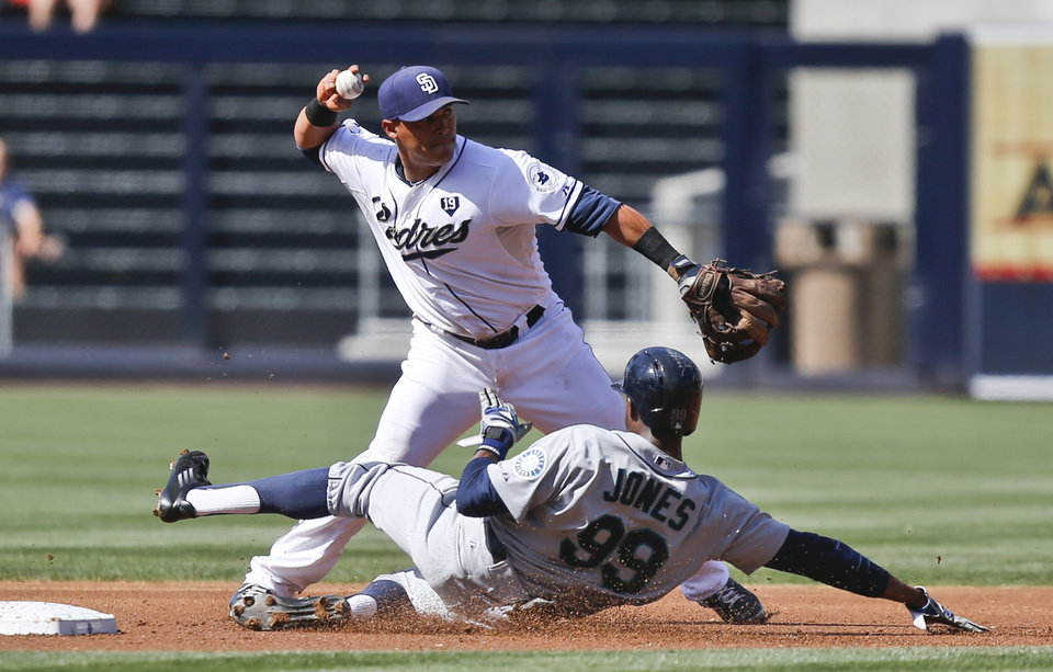 Photo - San Diego Padres shortstop Everth Cabrera throws to first to complete a double play as Seattle Mariners' James Jones (99) slides into second during the first inning of a baseball game, Thursday, June 19, 2014, in San Diego. (AP Photo/Lenny Ignelzi)