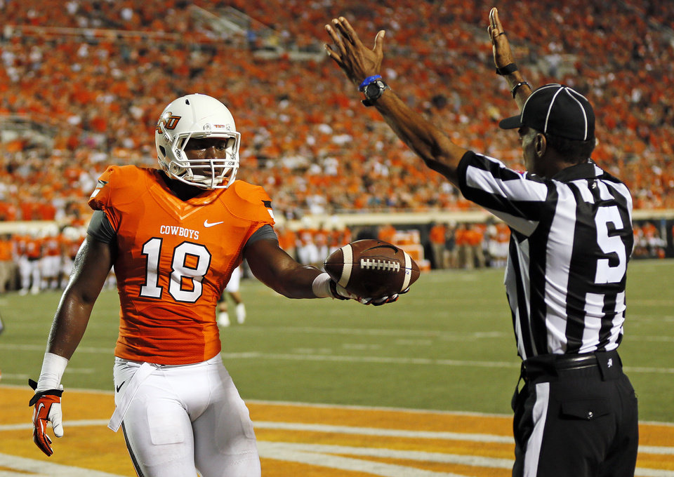 Photo - Oklahoma State's Blake Jackson (18) gives the ball to an official after a touchdown catch in the third quarter during a college football game between the Oklahoma State University Cowboys (OSU) and the Lamar University Cardinals at Boone Pickens Stadium in Stillwater, Okla., Saturday, Sept. 14, 2013. Photo by Nate Billings, The Oklahoman