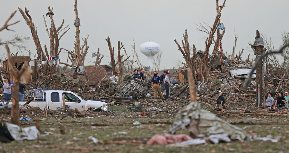 Emergency personal and others survey the scene in a neighborhood next to Plaza Towers Elementary School in Moore, Okla., after a tornado destroyed the neighborhood on Monday, May 20, 2013. Photo by Bryan Terry, The Oklahoman