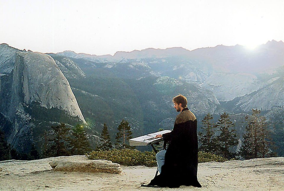 Composer Chance Thomas gets in the spirit of J.R.R. Tolkien\'s fantasy world in this provided photo. Thomas, seen wearing robes and playing a keyboard, has written scores for 10 computer and video games based on Tolkien\'s work. - Provided