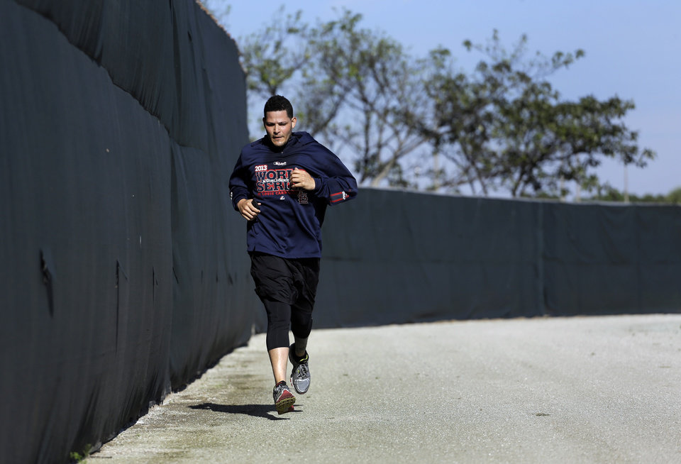Photo - St. Louis Cardinals catcher Yadier Molina jogs along a warning track during an informal spring training baseball practice Wednesday, Feb. 12, 2014, in Jupiter, Fla. Cardinals pitchers and catchers first official practice is scheduled for Thursday. (AP Photo/Jeff Roberson)