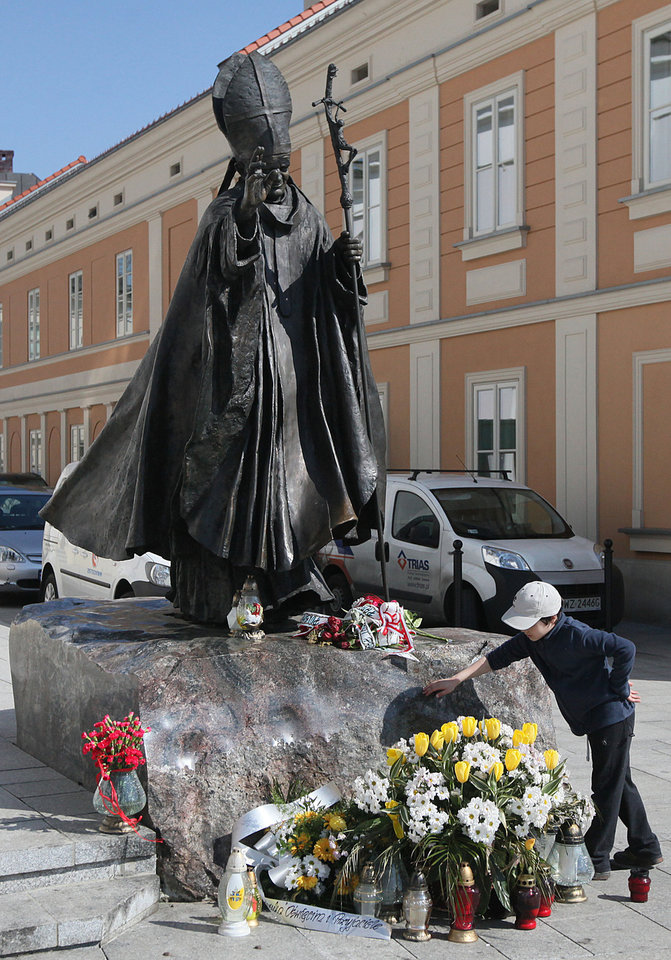 Photo - The figure of blessed Pope John Paul II is pictured before the Holy Mary' Offering Basilica where he was baptized as an infant in Wadowice, Poland, on Monday, April 7, 2014. The basilica neighbors the house where the pope was born as Karol Wojtyla in 1920 and where a multimedia museum will open in his memory on Wednesday, just over two weeks before he will be made a saint in a Vatican ceremony April 27. (AP Photo/Czarek Sokolowski)